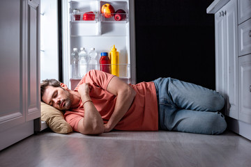 exhausted man sleeping on floor in kitchen near open refrigerator