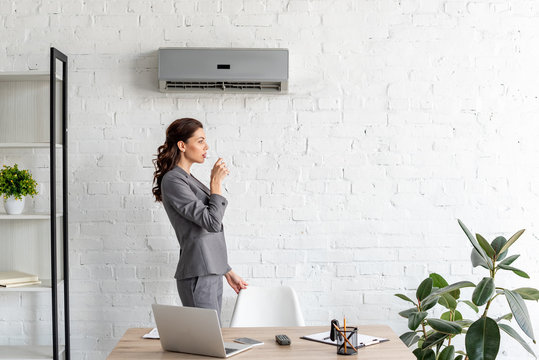 pretty businesswoman drinking water while standing near workplace under air conditioner