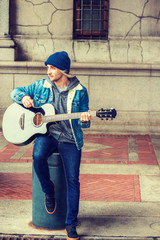 Street Musician in New York City. Young college student with long blonde hair, wearing blue Denim jacket coat, knitted hat, jeans, sneakers, sitting on vintage street on campus, playing guitar..