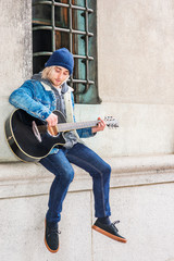 Street Musician in New York City. Young college student with long blonde hair, wearing blue Denim jacket coat, knitted hat, jeans, sneakers, sitting against wall by window on campus, playing guitar..