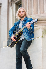 Musician Playing Guitar outdoor in New York City. Young handsome man with long blonde hair, wearing blue Denim jacket, black pants, gray shirt, playing guitar outside vintage style building, looking..