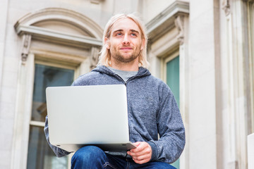 Man Working Outside. Young hipster college student with long blonde hair, wearing gray sweater with hood, sitting on street, outside old style office building in New York, working on laptop computer..