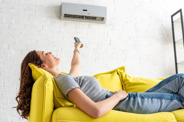 attractive young woman relaxing under air conditioner and holding remote control Wall mural