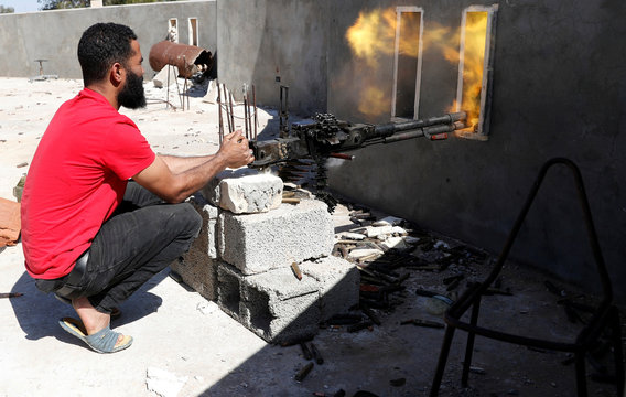 A fighter loyal to Libyan internationally recognised government fires a heavy machine gun during clashes with forces loyal to Khalifa Haftar at outskirts of Tripoli