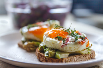 Breakfast served of two toasts with avocado, fried eggs with vegetables and herbs on a rustic tablecloth background. View from above. Healthy and nutritious food concept.