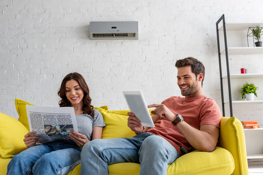 pretty woman reading newspaper and handsome man using digital tablet while sitting on yellow sofa under air conditioner at home