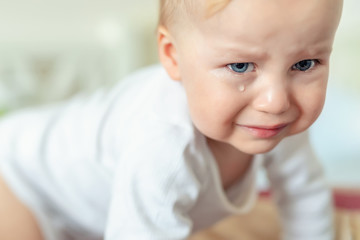 Cute caucasian blond toddler boy portrait crying at home during hysterics. Little child feeling sad. Little actor acting sadness emotions demanding something