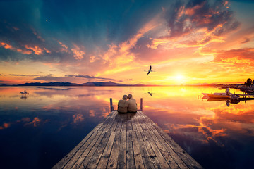 Printed kitchen splashbacks Sea sunset Senior couple seated on a wooden jetty, looking a colorful sunset on the sea with a flying flamingo reflected on the calm water.