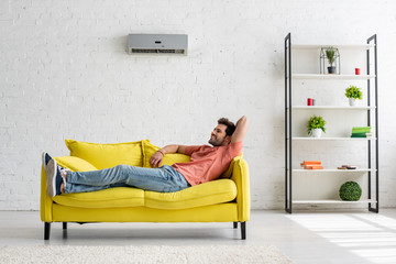 handsome smiling man lying on yellow sofa under air conditioner at home Wall mural