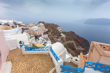 View of byzantine castle ruins and red cliffs from terrace of Oia village