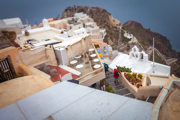 Tilt shift effect of terraces and houses of Oia on rainy day