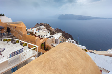 View of byzantine castle ruins and Oia village houses in a rainy day