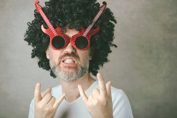 funny mature man with sunglasses doing rock symbol with hands up