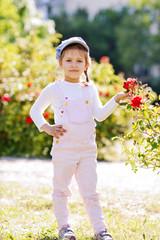 little girl near the roses bush