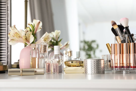 Luxury makeup products and accessories with perfumes on dressing table