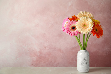 Wall Murals Gerbera Bouquet of beautiful bright gerbera flowers in vase on marble table against color background. Space for text