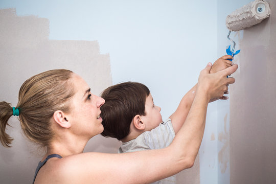 Mom teachs her 3 years son painting with roller at home