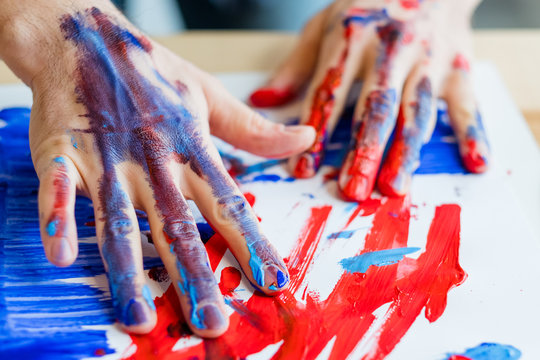 Man hands in red blue paint closeup. Fingers, paper smeared with acrylic oil gouache. Art therapy. Activity and creativity.