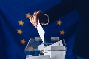 Man throwing his vote into the ballot box.
