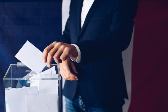 Elections in France. Man throwing his vote into the ballot box.