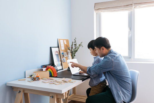 Boy sitting on father's lap behind desk in home office