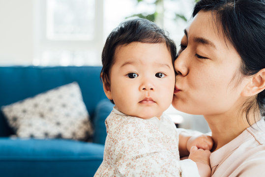 Adorable baby girl and her mother playing at home