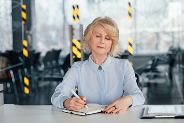 Senior corporate ceo busy making notes in diary. Confident business woman planning meeting presentation consultation.
