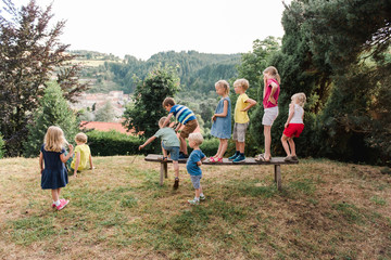 kids lining up on a bench with the intention of jumping off