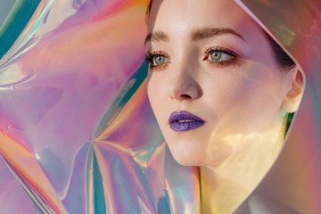 Surreal portrait of young beautiful woman with violet lips on holographic background and with unusual lightning