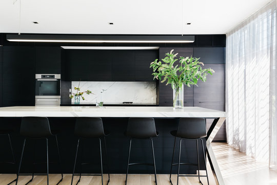 Stunning black contemporary kitchen with sheer curtains and marble counter top