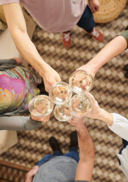 Above of arms toasting with wine glasses.