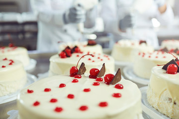 Red cherry on white cake on a table with cakes