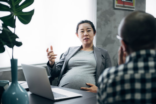 Pregnant woman and her colleagues  in the office