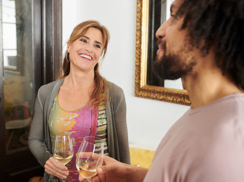 Attractive red-haired woman with glass of champagne smiling at f