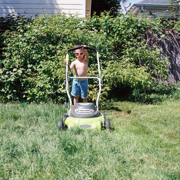 Six year old boy in shorts and sunglasses mows the lawn on a sunny day in Portland, Oregon
