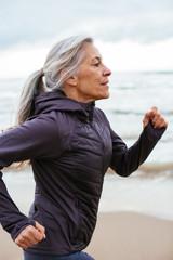 Active senior woman running on the beach.
