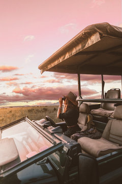 A girl sitting in a safari car trying to spot a game