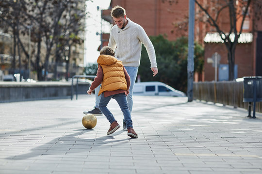 Dad with kid playing football in the street