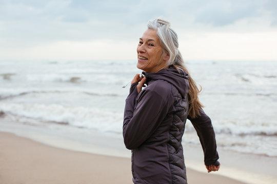 Active senior woman doing sport on the beach.