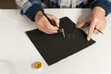 A Master Calligrapher writing elegant cursive lettering with a nib mounted on a oblique holder