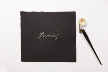 """the word """"Beauty"""" hand-written with silver ink, a tiny ink container and a nib mounted on a oblique holder are close to the paper."""