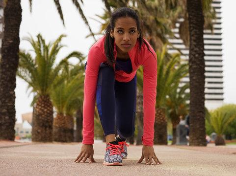 Focused black woman preparing for running
