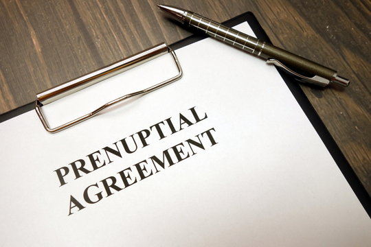 Clipboard with prenuptial agreement and pen on desk