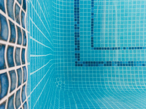 Tiled floor of an indoor heated swimming pool. UK.
