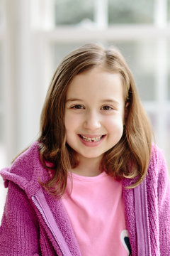 Beautiful young girl showing her first lost tooth