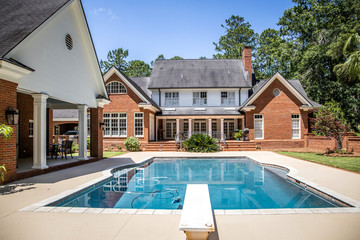 Large Blue Swimming Pool Outdoors with Brick Pool House and Home with pool Cleaner running