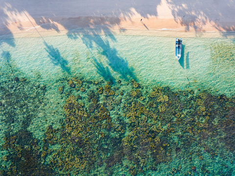 Aerial view of a woman walking on a sandy beach and a boat aground in Kapas Island, Malaysia