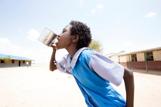 Side view of school girl drinking water