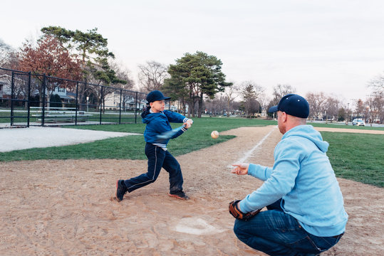 Father and son practicing hitting ball on a baseball field