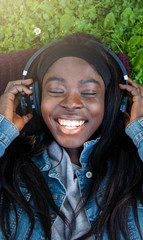 Young African woman listening to music lying in the park.